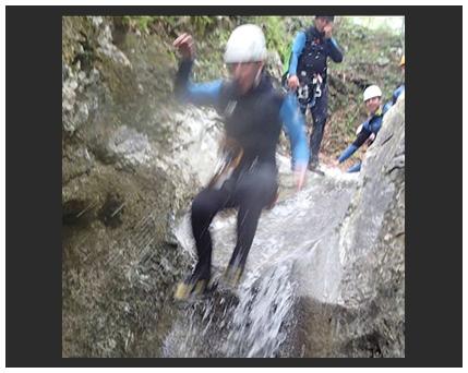 boy jumping down waterfall photo